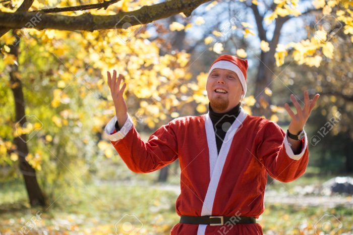 Man in santa claus stand among fallen leaves in autumnal park
